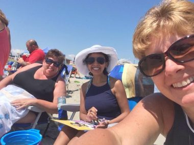 Patty, Nicole, and Julie smile while sitting in chairs on the beach. / Cystic Fibrosis News Today