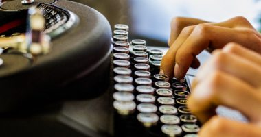 writing \ Cystic Fibrosis News Today \ Two hands type away on an old-fashioned manual typewriter