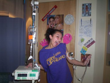 """Cystic Fibrosis News Today \ A 2007 photo shows Nicole in the hospital """"modeling"""" a purple T-shirt and wearing a funny smile"""