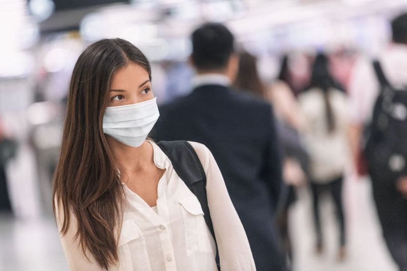 freedom and COVID-19 pandemic / Cystic Fibrosis News Today / photo of woman wearing a face mask in a crowded room