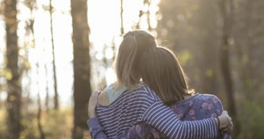Cystic Fibrosis News Today \ A stock image of two women - either sisters or friends - hugging in a forest, with bright, out-of-focus sunlight piercing the trees in the background