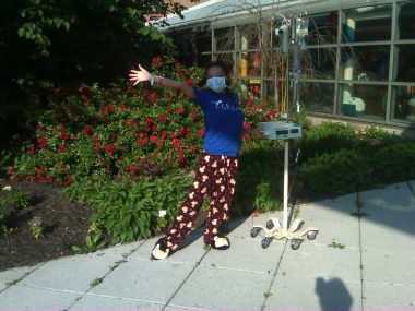 Hospitalization / Cystic Fibrosis News Today / Nicole wears pajama pants and a face mask while standing outside the hospital with her IV pole.