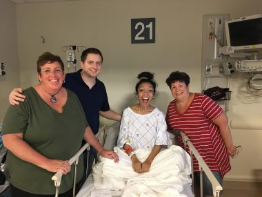 lung transplant | Cystic Fibrosis News Today | Nicole's mom, husband, and aunt stand around Nicole in her hospital bed and gown as she prepares to go into surgery for a bilateral lung transplant in Pennsylvania